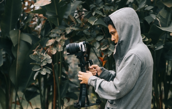 Canva - Man in Hooded Jacket Holding Camera With Stablizer