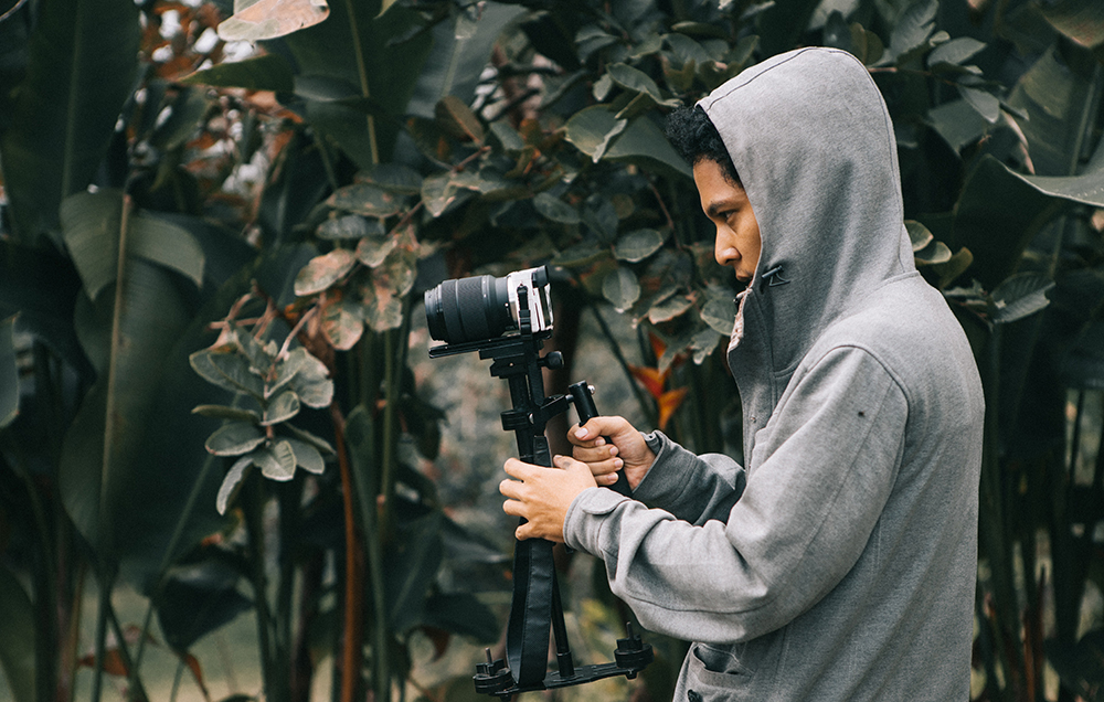 canva-man-in-hooded-jacket-holding-camera-with-stablizer-3