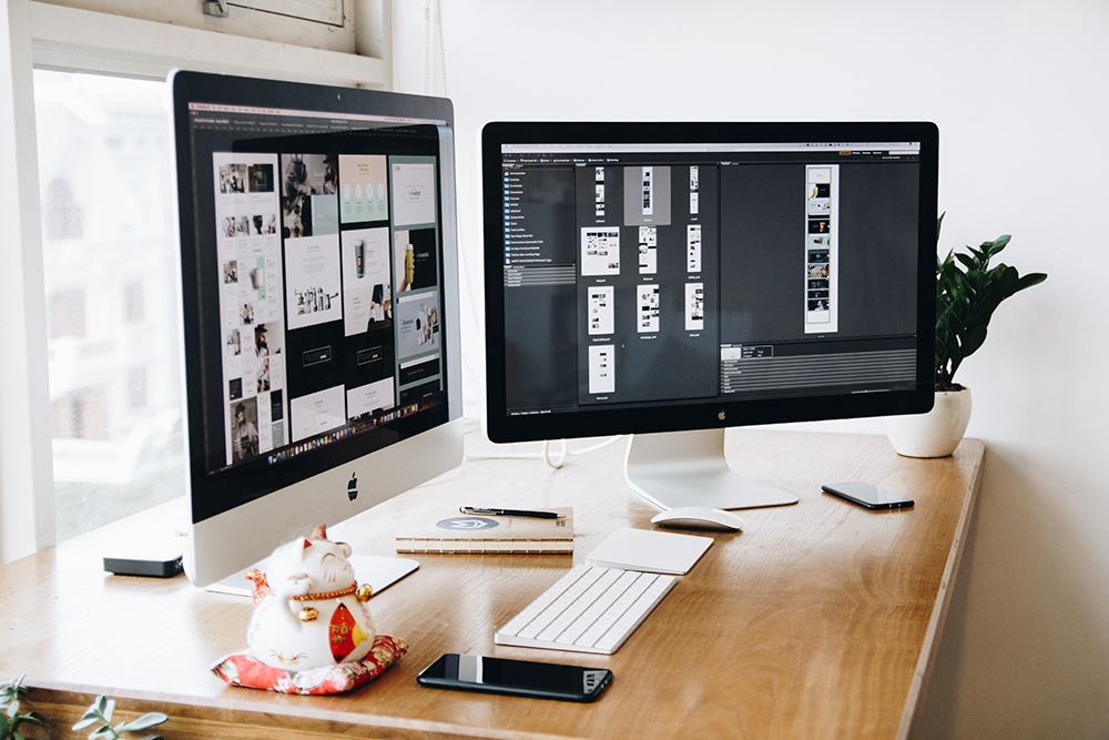 canva-two-imacs-with-keyboard-and-phones-on-desk